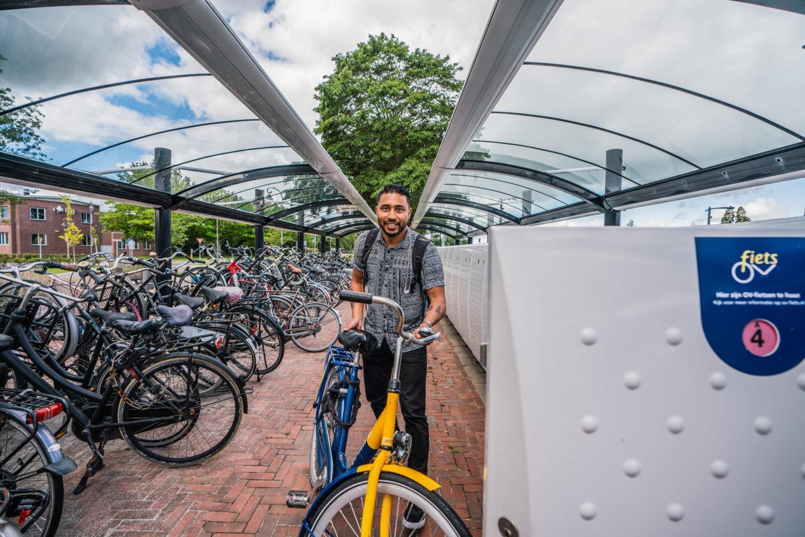 Een man gebruikt een fietskluis op een hub.