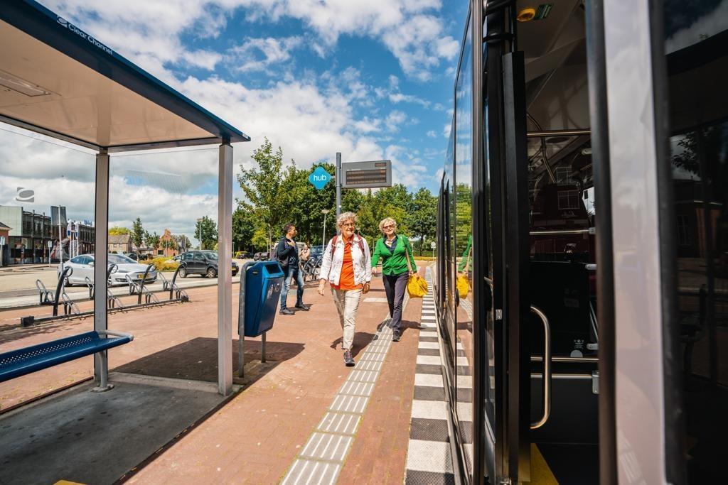 Twee vrouwen lopen in de richting van een bus op een hub.