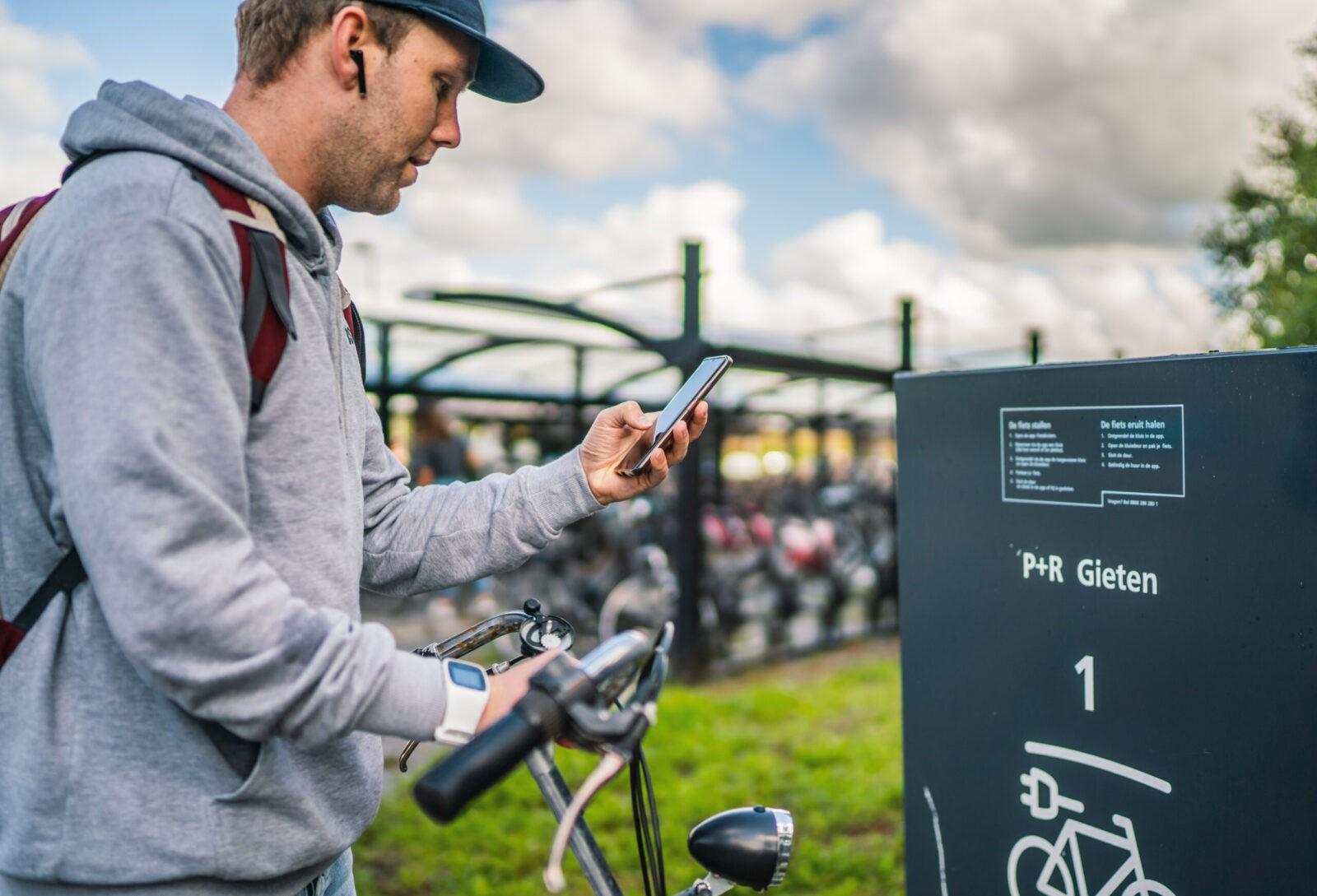 Een man gebruikt op zijn mobiel de app 'Fietskluizen' om een fietskluis te openen op een hub.