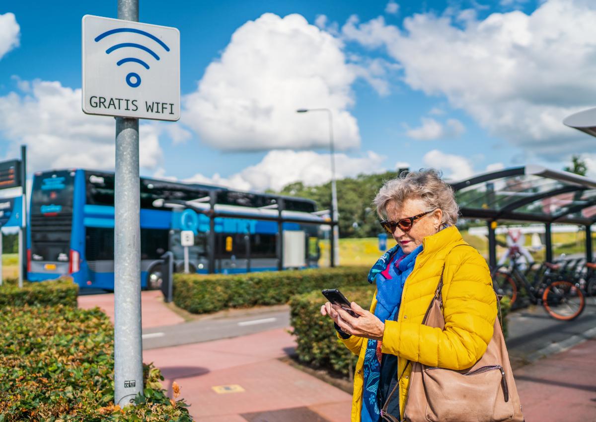 Een vrouw gebruikt de gratis WiFi op een hub.