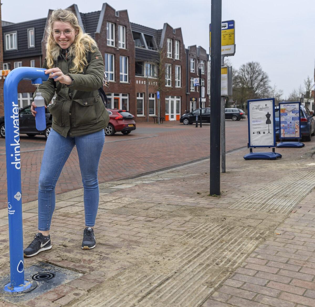 Meisje vult flesje water bij watertappunt op Groningse hub