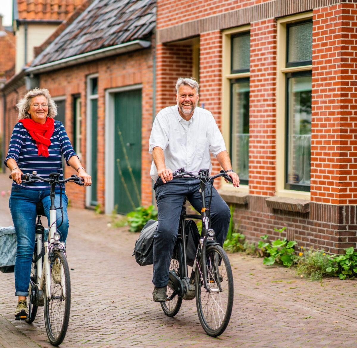 Man en vrouw op fiets door Winsum